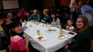 People from different countries sitting around a table having a potluck dinner