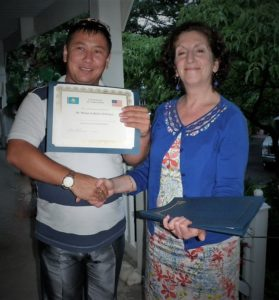 Gail shakes the hand of a young man of Asian descent and give him a certificate of completion